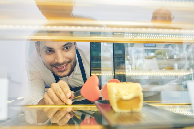 Cameriere che prende la torta dalla vetrina