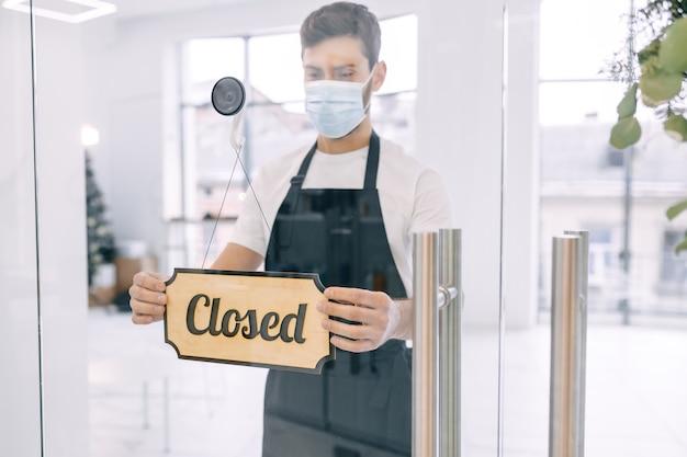 Un cameriere che indossa una maschera protettiva trasforma un cartello con testo chiuso su una porta di vetro in un moderno caffè