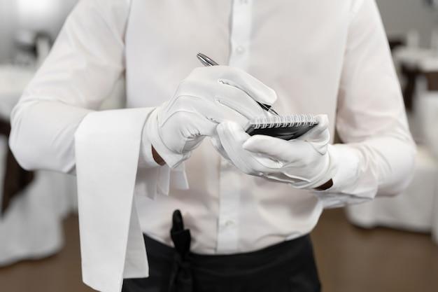 Cameriere in camicia bianca e papillon che annota un ordine in un bar, primo piano.