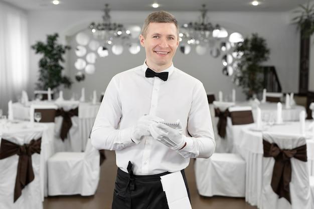 Cameriere in camicia bianca e papillon che annota un ordine in un caffè.
