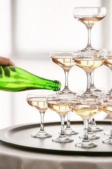 Cameriere con bottiglia e torre di bicchieri con champagne sul tavolo