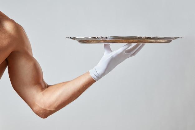 Cameriere con mano muscolare in un guanto bianco che tiene un vassoio vuoto di metallo