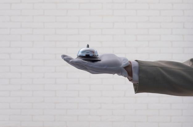 Una mano dei camerieri in un guanto bianco con un campanello