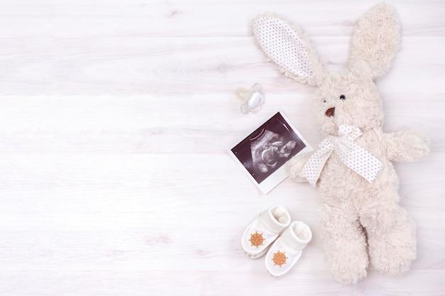 Aspettando il bambino. ragazzo. ecografia dell'immagine del feto nell'utero di una donna incinta e un coniglietto giocattolo, un capezzolo e calzini per un neonato su uno sfondo di legno chiaro.