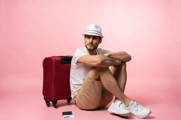 Aspettando il volo. viaggiatore dell'uomo seduto sul pavimento con la valigia.