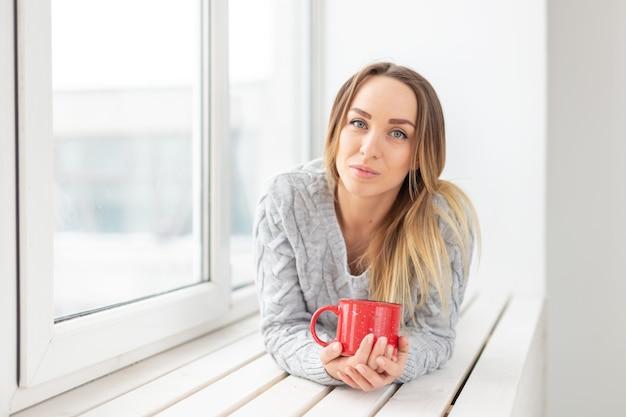 In attesa, solitudine e concetto di bellezza - giovane donna con una tazza di tè caldo seduto sul davanzale della finestra