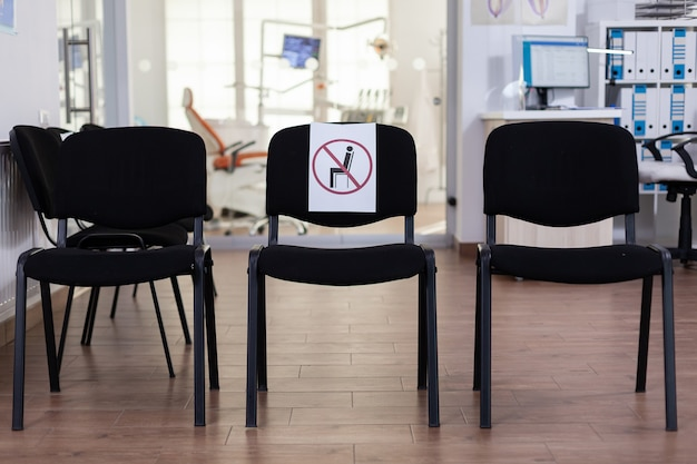 Sala d'attesa in clinica senza nessuno, front office con nuova normalità con segno sulla sedia per la distanza sociale nella pandemia di coronavirus. ricezione di stomatologia vuota durante l'epidemia di covid-19.