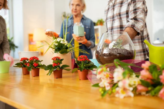 In attesa del loro turno. bellissimi fiori in piedi sul tavolo mentre aspettano il loro turno