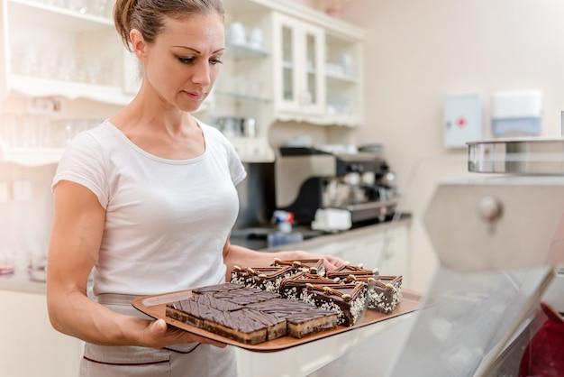 Cameriera organizzando la torta in vetrina