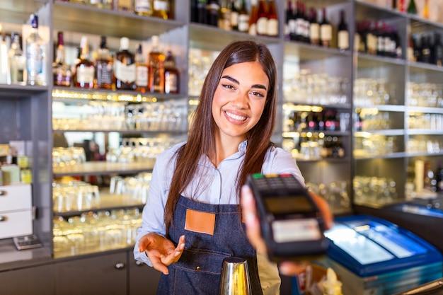Cameriera al banco cassa che tiene una macchina di pagamento con carta elettronica.