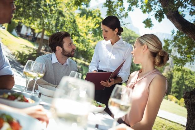 Cameriera che discute il menu con il cliente nel ristorante