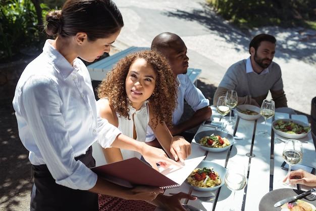 Cameriera che discute il menu con la donna nel ristorante