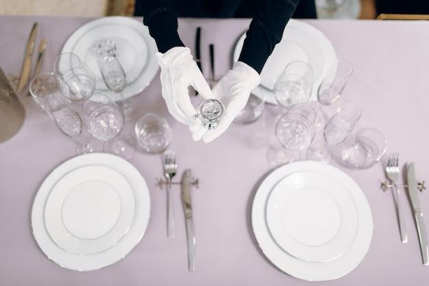 Cameriera in guanti mette i piatti, apparecchiare la tavola, vista dall'alto. servizio di servizio, decorazioni per la cena festiva, stoviglie per le vacanze