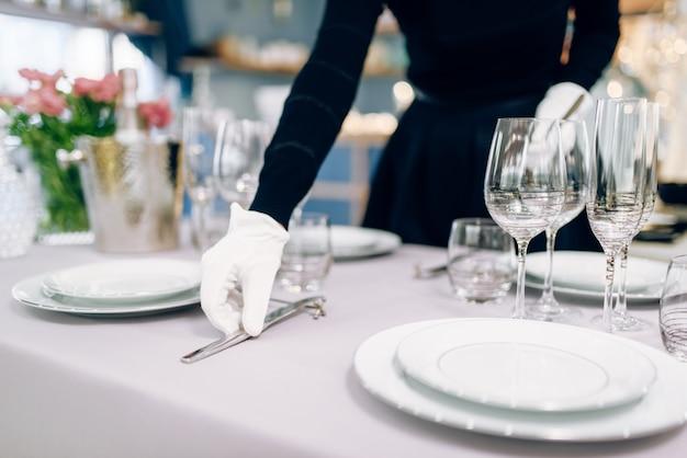 Cameriera in guanti mette il coltello, apparecchiare la tavola. servizio di servizio, decorazioni per la cena festiva, stoviglie per le vacanze