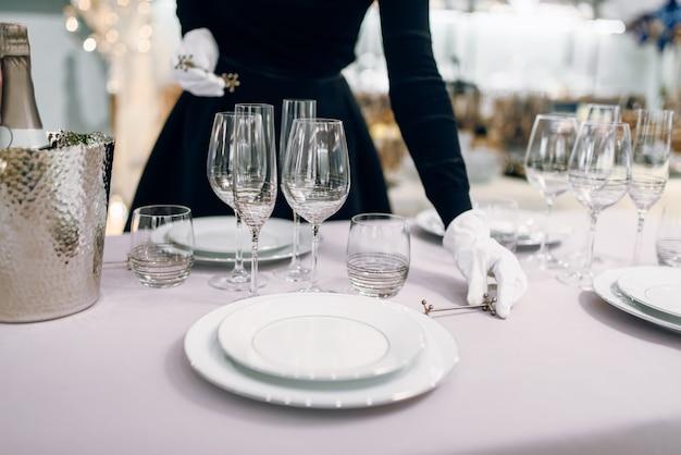 Cameriera in guanti mette il coltello, apparecchiare la tavola