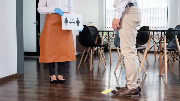 La cameriera teneva un cartello che spiegava l'allontanamento sociale ai clienti