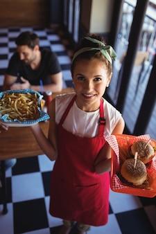 Cameriera che tiene hamburger e patatine fritte nel vassoio