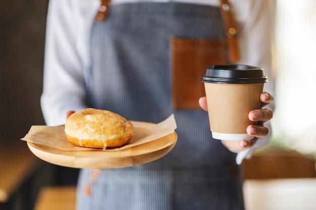 Una cameriera in possesso e servire un pezzo di ciambella fatta in casa nel vassoio di legno e una tazza di caffè di carta