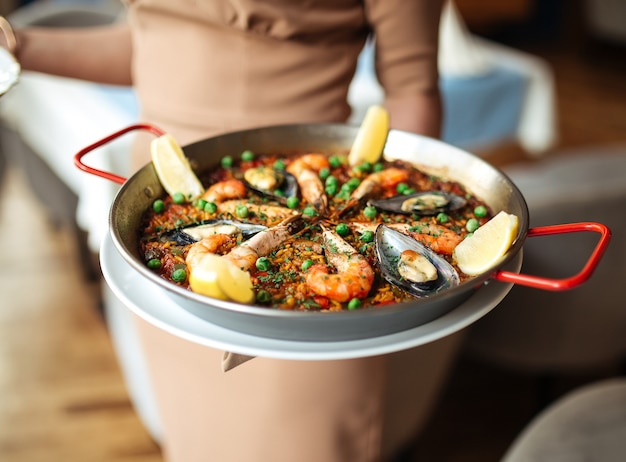 Cameriera che tiene paella di piatto di riso nazionale spagnolo con frutti di mare