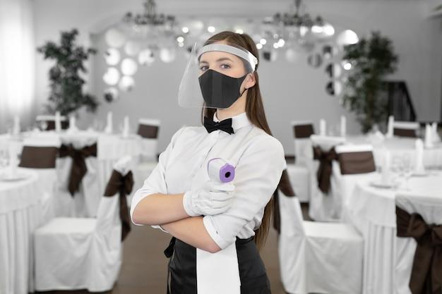 La cameriera è una donna che indossa una maschera facciale e tiene un termometro a infrarossi sulla fronte per controllare la temperatura corporea per i sintomi del virus nei clienti