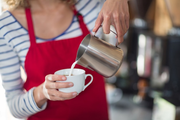 Cameriera di bar che produce tazza di caffè al bancone in caffè
