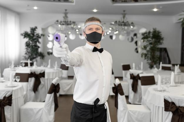 Cameriera che indossa una maschera facciale e tiene un termometro a infrarossi sulla fronte per controllare la temperatura corporea per i sintomi del virus nei clienti