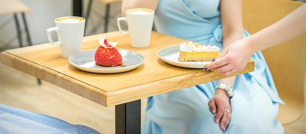 La mano della cameriera mette il pezzo di cupcake sul tavolo in un bar, la mano della donna sta mettendo una piccola pasticceria rotonda sul tavolo su uno sfondo di una donna in un vestito blu