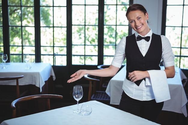 Cameriera che mostra un tavolo
