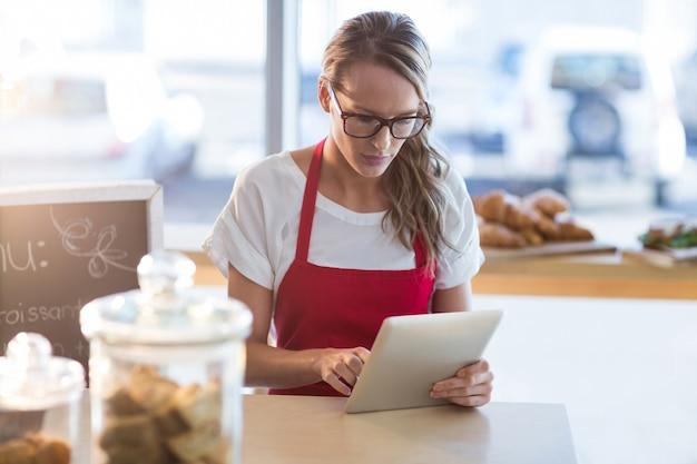 Cameriera seduto al tavolo e utilizzando la tavoletta digitale