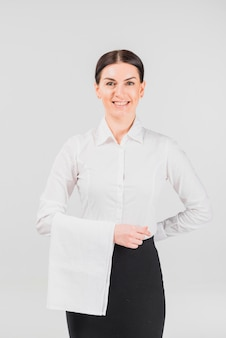Cameriera sorridente e tenendo la mano dietro la schiena