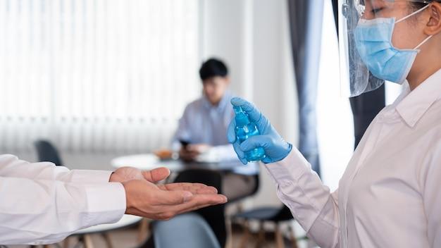 Il personale delle cameriere usa alcool o gel disinfettante spray per prevenire la diffusione della pandemia covid-19