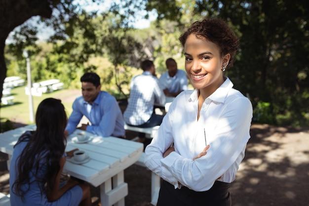 Cameriera in piedi con le braccia incrociate al ristorante all'aperto