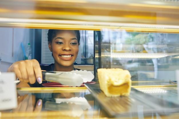Cameriera prendendo la torta dal display