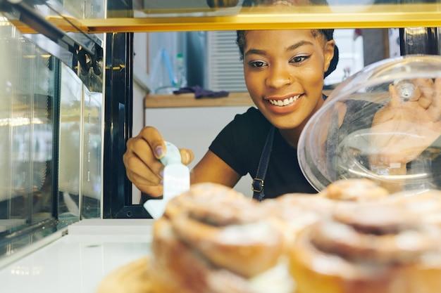Cameriera prendendo pasticceria dalla vetrina