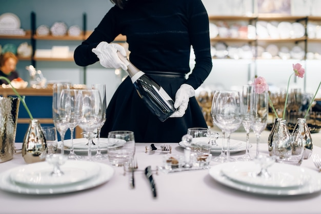 Cameriera con una bottiglia di champagne, tavola. servizio di servizio, decorazioni per la cena festiva, stoviglie per le vacanze