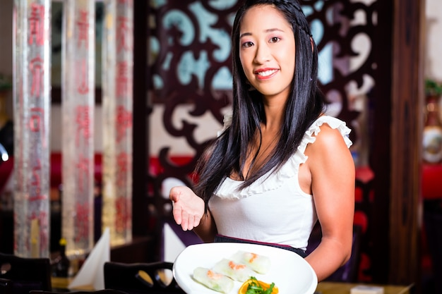 Cameriera con sushi nel ristorante asiatico