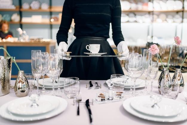 Cameriera con un vassoio mette i piatti, apparecchiare la tavola. servizio di servizio, decorazione di cene festive, stoviglie per feste, stoviglie