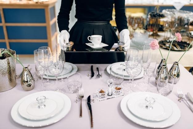 Cameriera con vassoio mette i piatti, apparecchiare la tavola