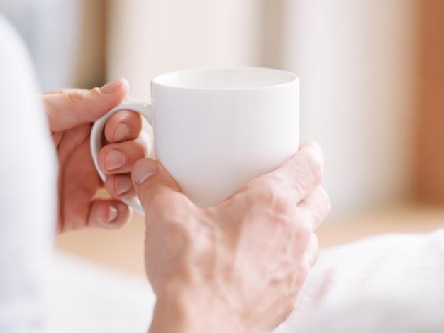 Bevanda sveglia. mani dell'uomo con la tazza bianca della bevanda calda del mattino. avvicinamento.