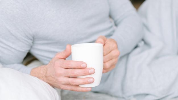 Bevanda sveglia. uomo sdraiato a letto e che tiene tazza bianca di tè caldo del mattino.