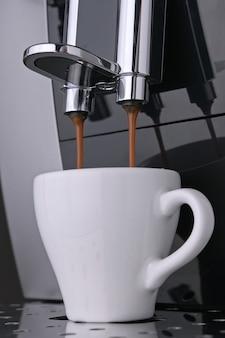Wake-up coffee espresso con chicchi di caffè arabica tostati scorre sotto pressione nella tazza bianca
