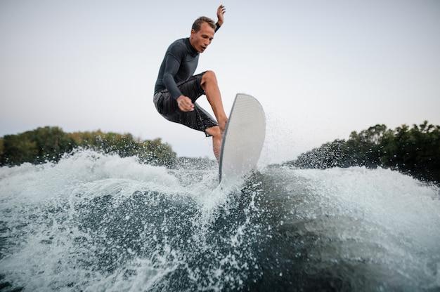 Wakeboarder che salta sull'onda di spruzzi blu