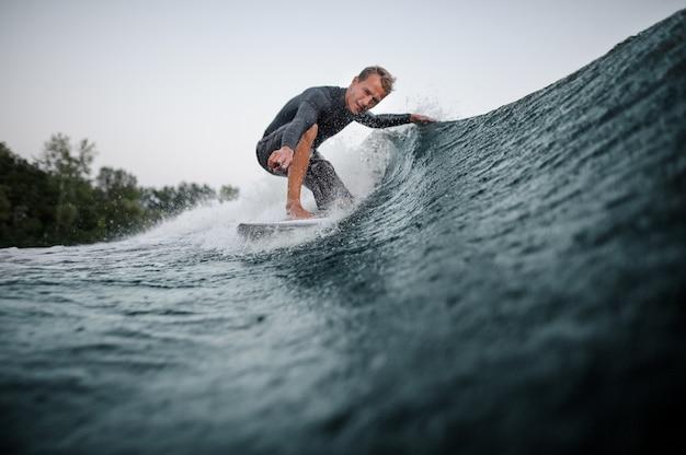 Wakeboarder cavalcando l'onda blu