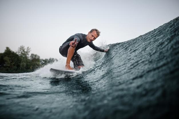 Wakeboarder cavalcando e toccando l'onda blu