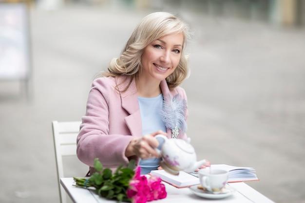 Cammina per la città ragazza bionda nei toni del rosa e del blu caffè all'aperto è primavera bevi il tè