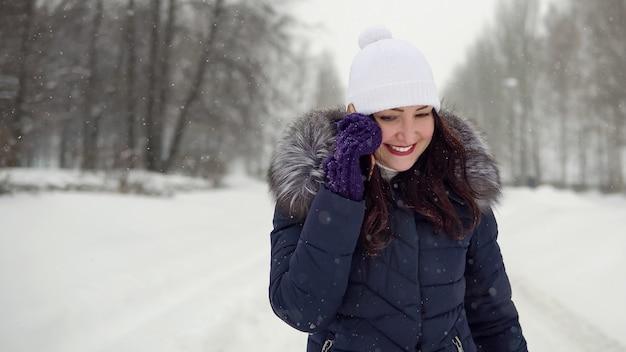 Cammina all'aria aperta. giovane donna che parla al telefono nel parco, copia spazio