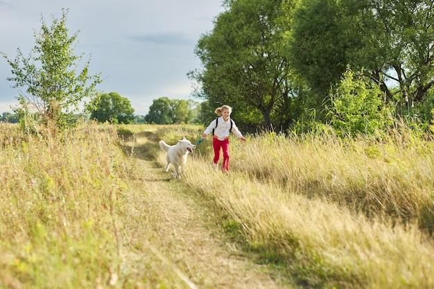 Cammina ragazza con cane in natura, esegui bambino con animale domestico nel prato soleggiato