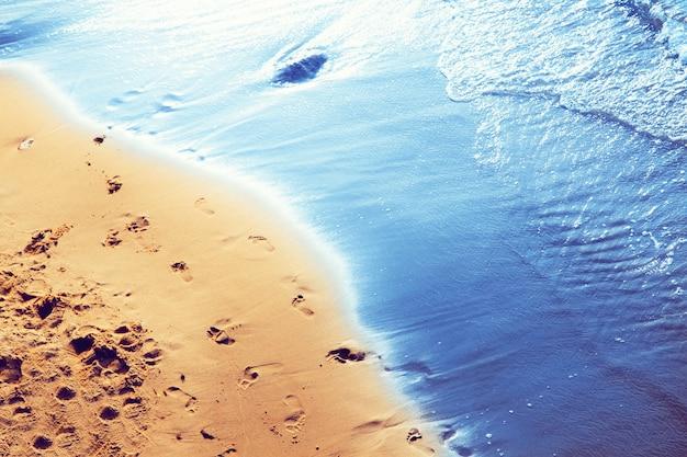 Camminare sulla spiaggia, lasciare impronte sulla sabbia.