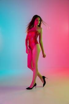 A piedi. bella ragazza seducente in costume da bagno rosso alla moda su sfondo rosa-blu sfumato alla luce al neon. ritratto a figura intera. copyspace per l'annuncio. estate, moda, bellezza, concetto di emozioni.
