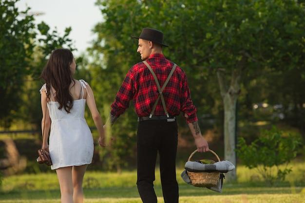 Scendendo. coppia giovane e felice caucasica che si gode il fine settimana insieme nel parco il giorno d'estate
